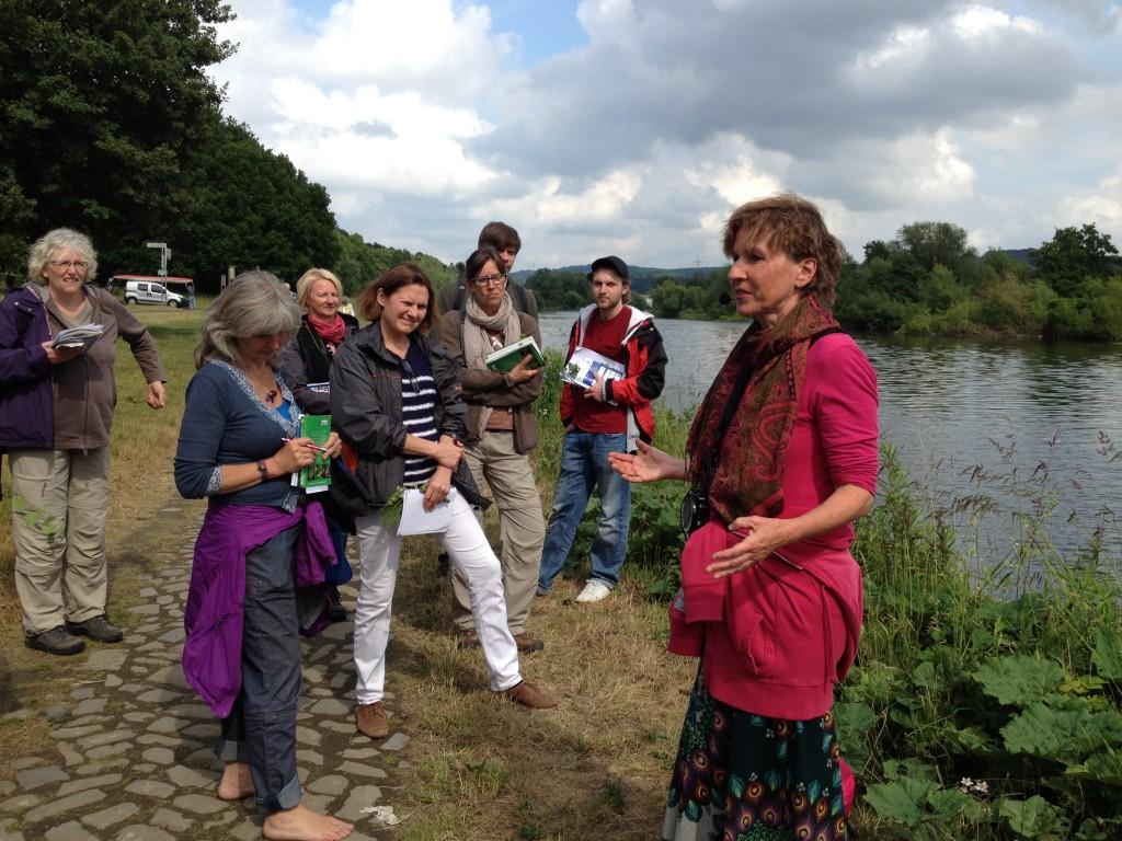Eine Gruppe hört auf der Kräutertour de Ruhr am Flussufer in Bochum der Biologin und Wildkräuter-Fachfrau Ursula Stratmann zu (Copyright: wilderwegesrand.de)